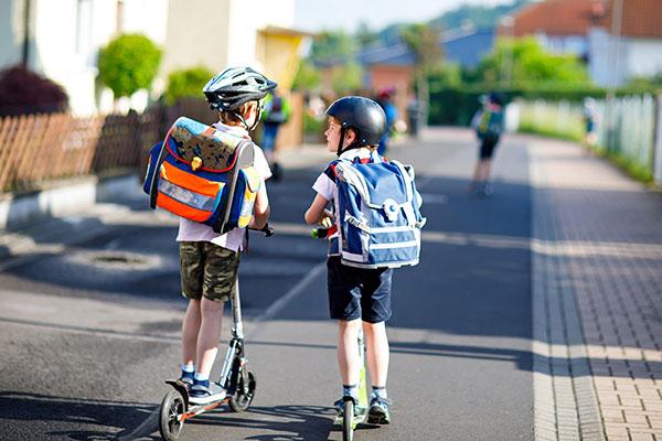 Kinder mit dem Roller auf dem Schulweg