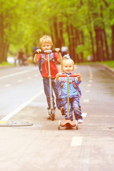 Kleiner Junge bringt seine kleine Schwester mit dem Roller zur Kita